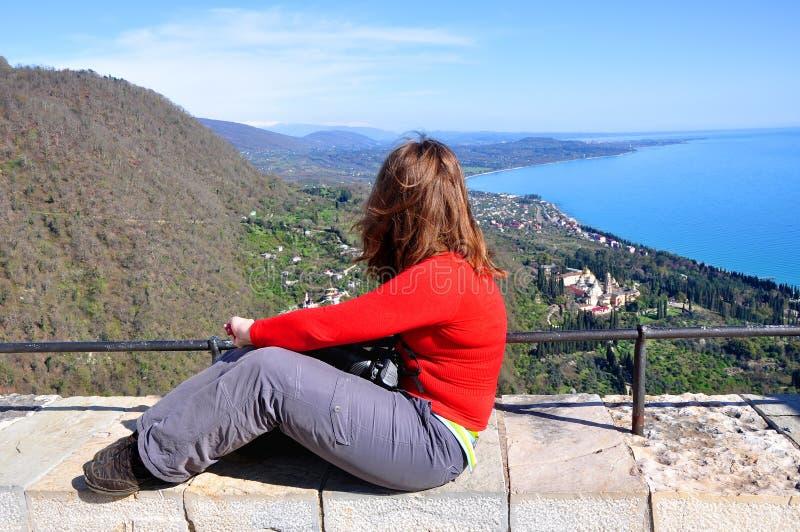 Una donna si siede su una piattaforma di osservazione e guarda dall'alto in basso la città Novy Afon, Abkhazia immagine stock libera da diritti