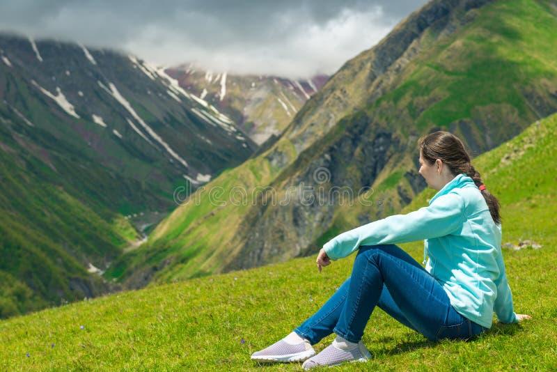 Una donna si siede sull'erba ed ammira il bello paesaggio della montagna fotografie stock libere da diritti