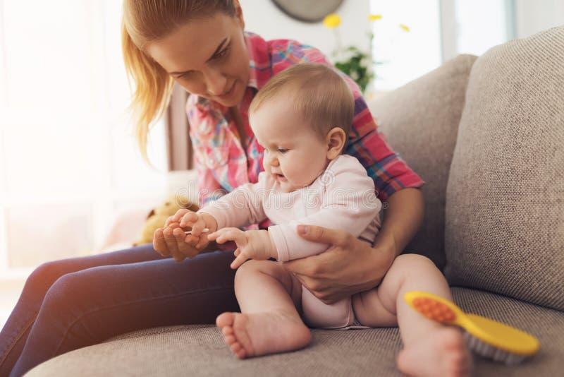 Una donna si siede sullo strato e pulisce i suoi chiodi Il bambino gradisce quando la mamma tocca le sue dita fotografia stock