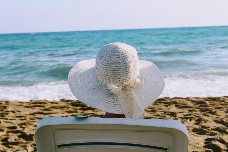 Una donna si siede in uno sdraio contro lo sfondo di una spuma del mare in un cappello bianco con l'ampio bordo fotografie stock libere da diritti