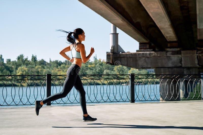 Una donna sportiva che corre all'aperto per fiume fotografie stock