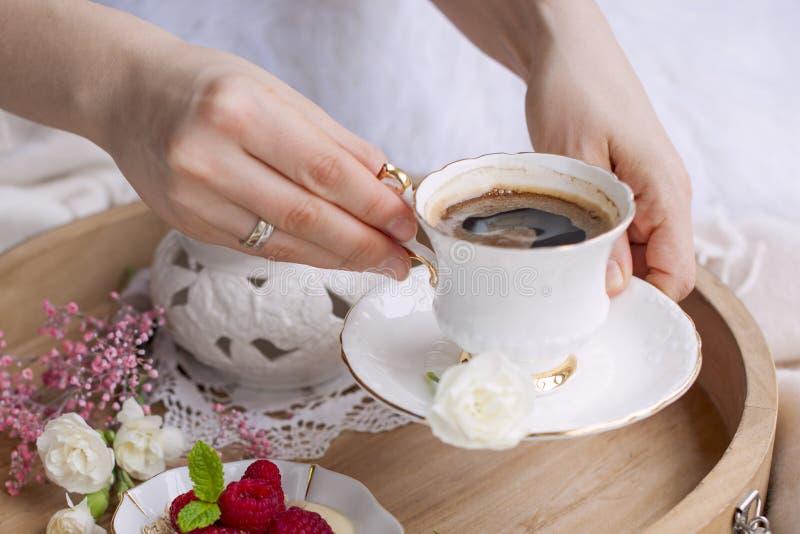Una donna sta bevendo il caffè a letto Un vassoio di legno con le bacche ed i fiori del lampone della prima colazione Colori chia fotografie stock