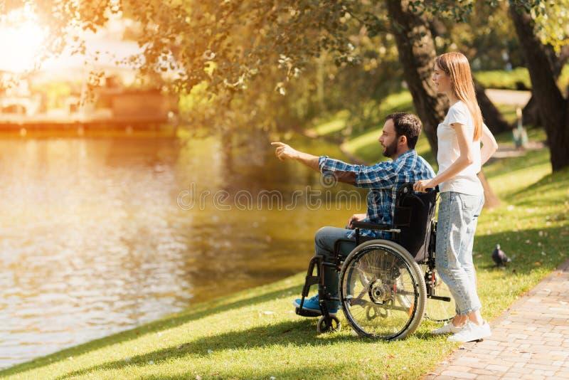 Una donna sta camminando nel parco con un uomo in una sedia a rotelle Sono sulla riva di un lago fotografia stock libera da diritti