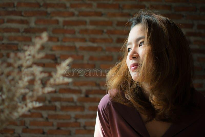 Una donna sta comperando su Internet mentre metteva il poco sorriso sul suo fronte immagini stock
