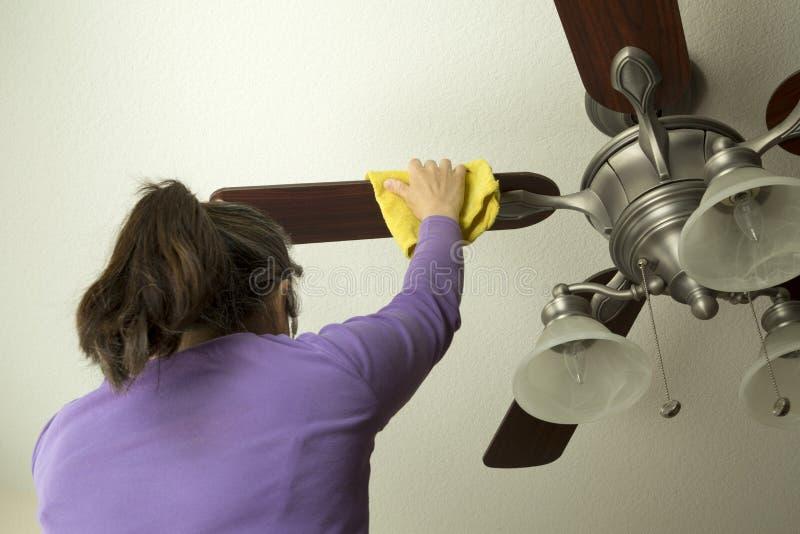 Una donna sta pulendo il ventilatore da soffitto immagini stock libere da diritti
