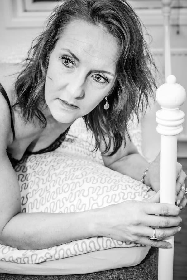 Una donna sta sdraiando nel suo letto immagini stock libere da diritti