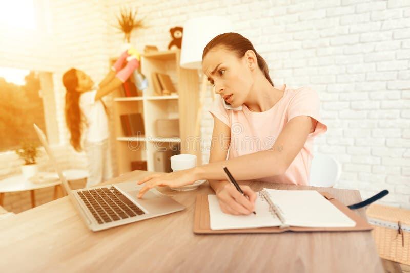 Una donna sta sedendosi ad una tavola vicino ad un computer portatile e ad un lavoro fotografia stock