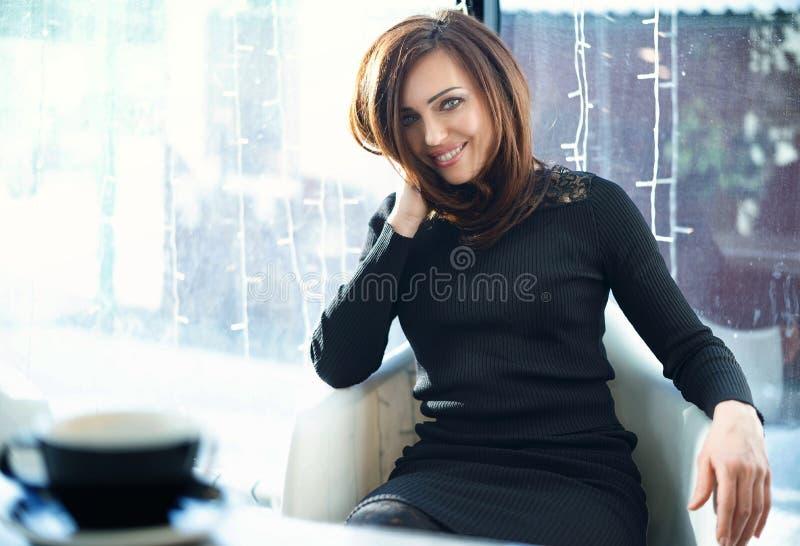 Una donna sta sedendosi in un caffè Primo piano, esaminante la macchina fotografica fotografie stock