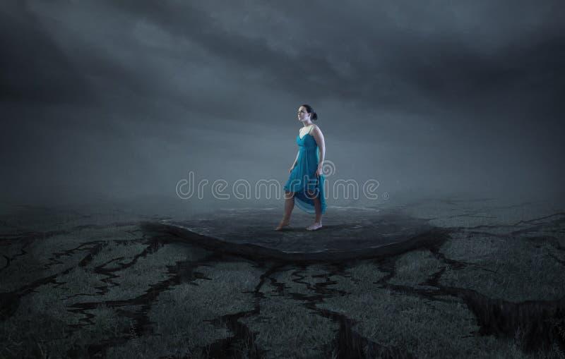 Una donna sta su una roccia compatta fotografia stock
