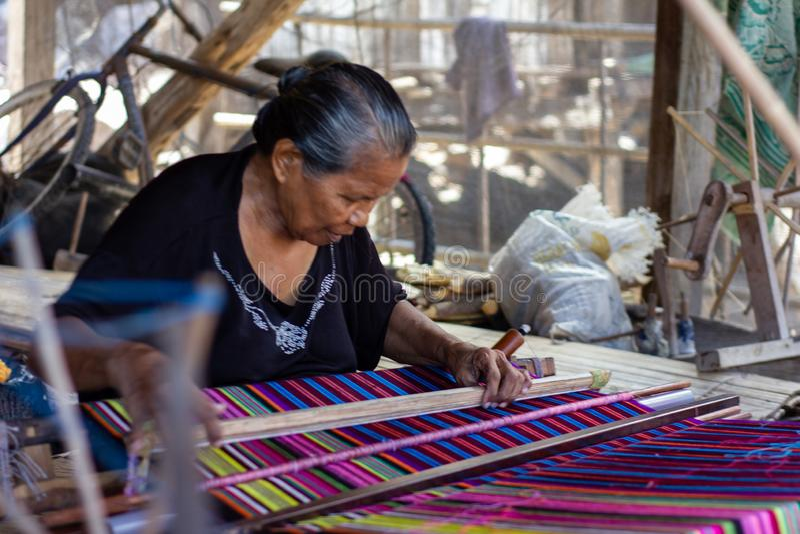 Una donna sta tessendo i tessuti variopinti tradizionali del Flores Tutti i processi di tessitura utilizzano l'attrezzatura manua fotografia stock