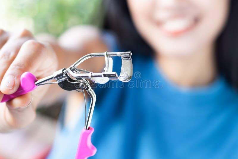 Una donna sta utilizzando il bigodino del ciglio fotografie stock