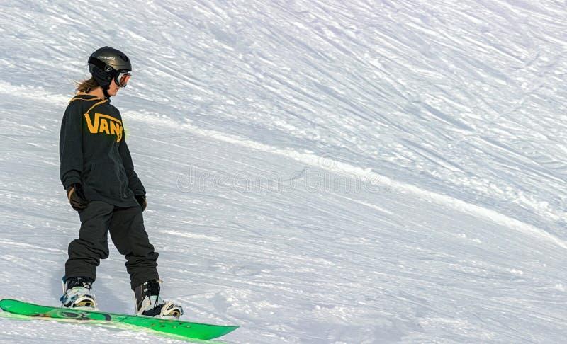 Una donna su uno snowboard che fa scorrere giù la montagna fotografia stock