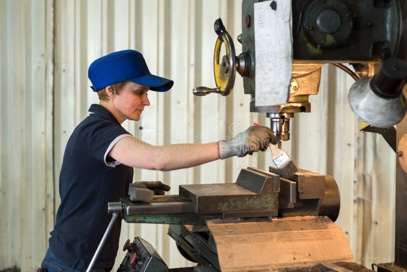 Una donna sul lavoro su una fresatrice verticale Lavorando di una parte di metallo su una macchina per il taglio di metalli fotografia stock libera da diritti