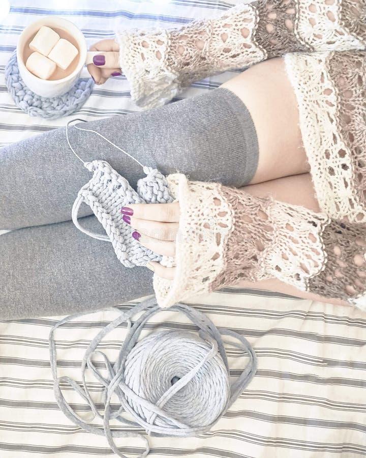 Una donna sul letto tricotta una sciarpa immagine stock
