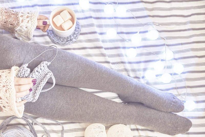 Una donna sul letto tricotta una sciarpa immagini stock
