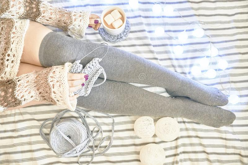 Una donna sul letto tricotta una sciarpa fotografia stock libera da diritti