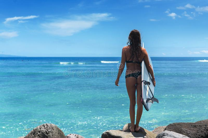 Una donna surfista indossa bikini con una tavola blu sullo sfondo dell'oceano e il cielo azzurro con nuvole fotografia stock libera da diritti