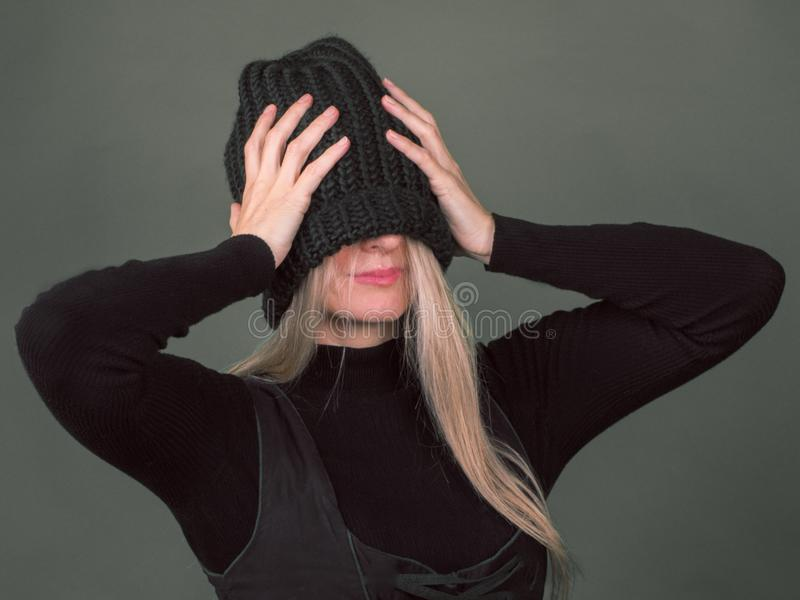 Una donna timida la tira un cappello tricottato sopra il suo fronte fotografie stock libere da diritti
