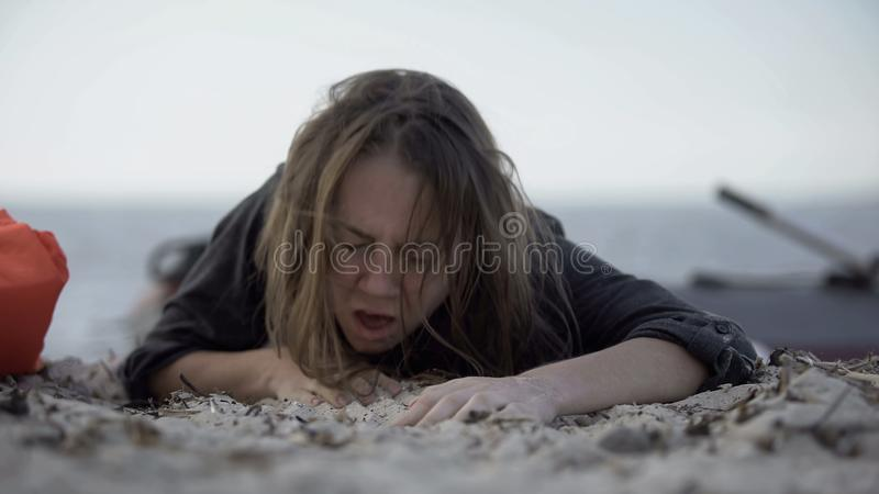 Una donna tossisce, cerca di strisciare sulla sabbia, sopravvivendo a una catastrofe naturale, vittima fotografie stock libere da diritti