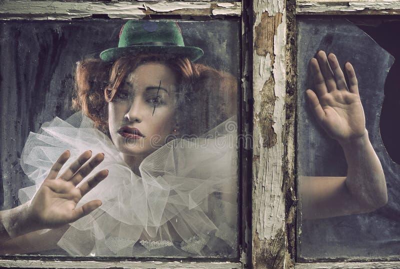 Una donna triste sola del pierrot dietro il vetro immagine stock