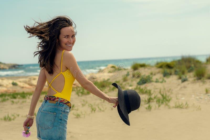 Una donna in un costume da bagno ed in un denim gialli mette la camminata in cortocircuito sulla spiaggia fotografia stock libera da diritti