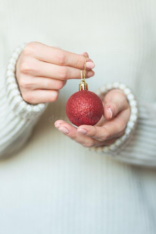 Una donna in un maglione di lana caldo luminoso che tiene le palle rosse nelle mani, spazio della copia, fuoco selettivo di un gi fotografie stock libere da diritti