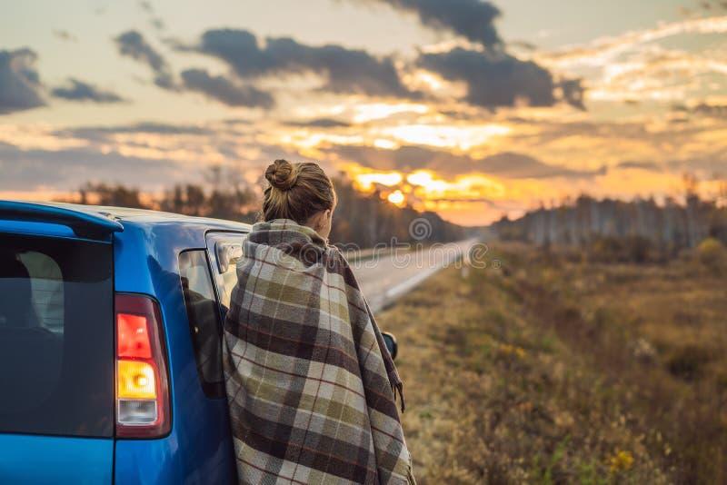 Una donna in un plaid fa una pausa l'automobile dal lato della strada nei precedenti dell'alba Concetto di viaggio stradale fotografie stock