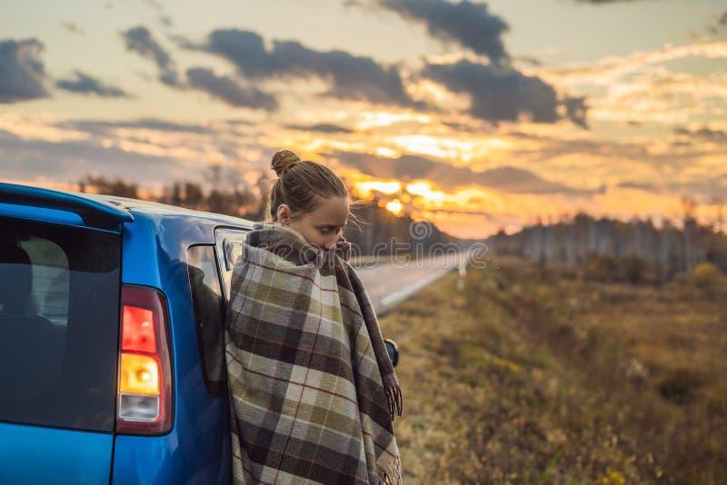 Una donna in un plaid fa una pausa l'automobile dal lato della strada nei precedenti dell'alba Concetto di viaggio stradale fotografia stock