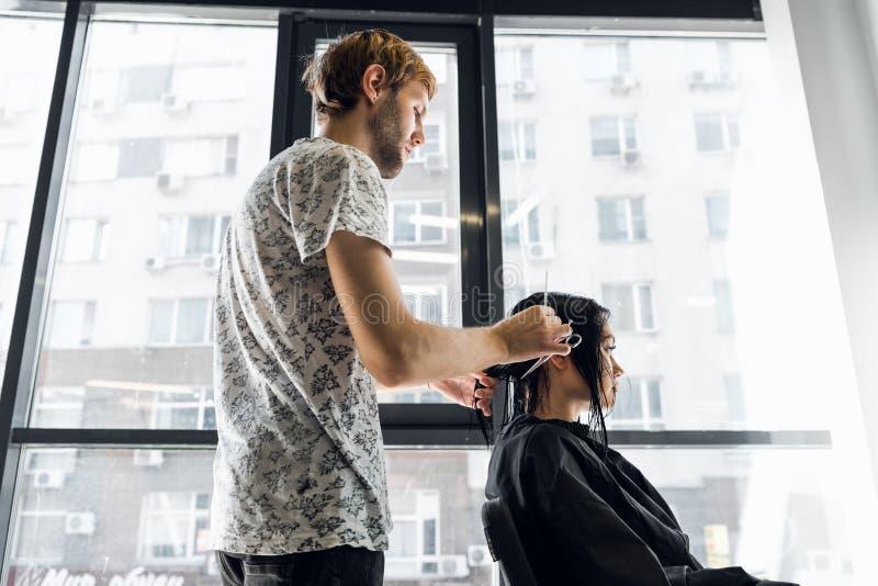 Una donna in un salone di lavoro di parrucchiere che aspetta per vedere i risultati guardare in uno specchio, sorridere e parlare immagine stock
