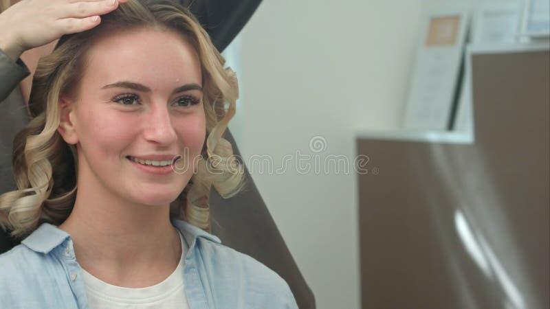 Una donna in un salone di lavoro di parrucchiere che aspetta per vedere i risultati di torsione dei riccioli, guardando in uno sp immagini stock