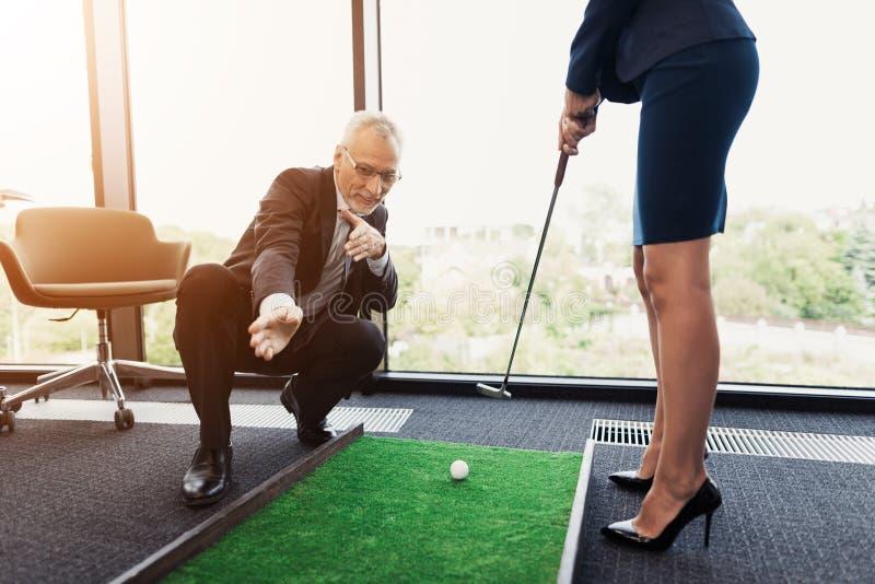 Una donna in un vestito dal nero gioca il golf nell'ufficio Un uomo anziano in un vestito la aiuta fotografia stock