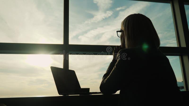 Una donna in un vestito guarda fuori la finestra del suo ufficio Concetto - sguardo in avanti nell'affare immagini stock libere da diritti