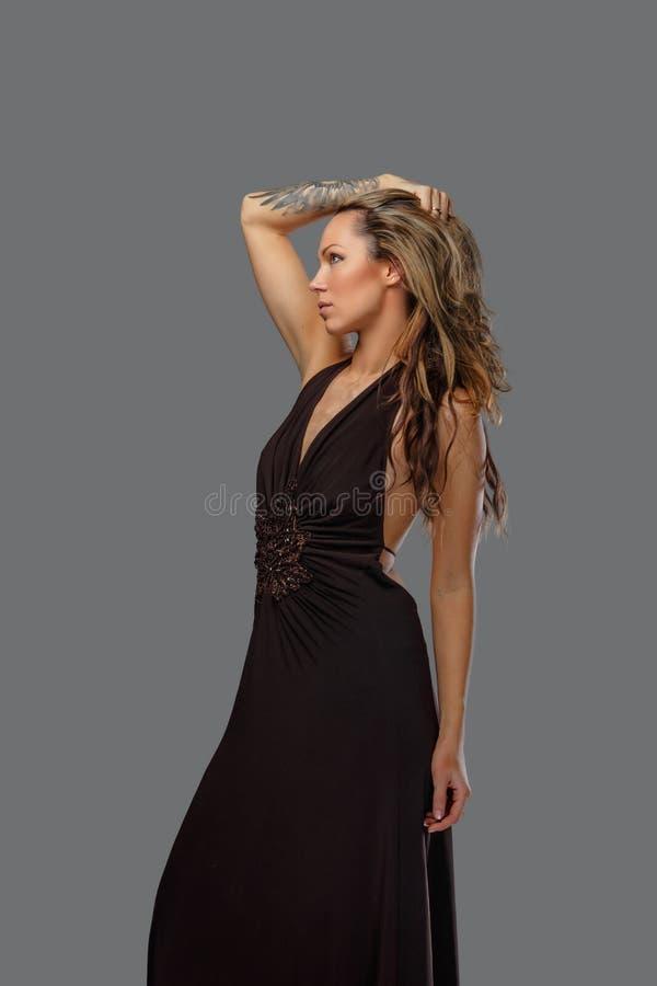 Una donna in un vestito marrone con il tatuaggio sul suo braccio fotografia stock libera da diritti