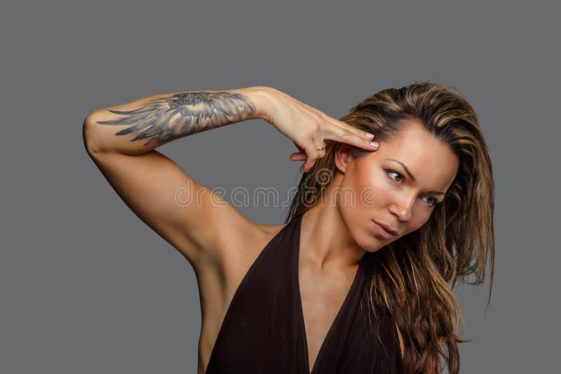 Una donna in un vestito marrone con il tatuaggio sul suo braccio immagini stock libere da diritti
