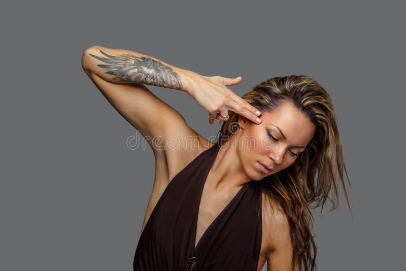 Una donna in un vestito marrone con il tatuaggio sulla sua mano immagini stock