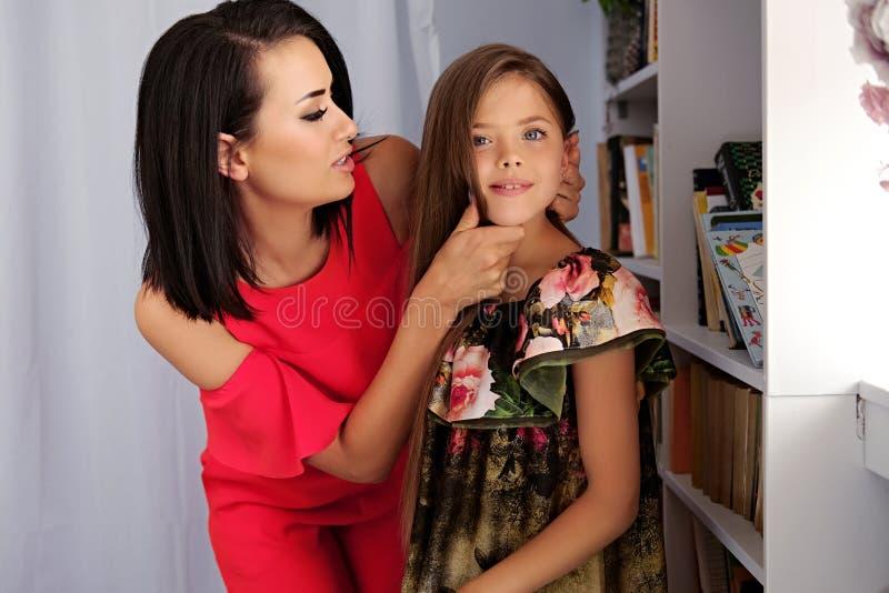Una donna in un vestito rosso che abbraccia un adolescente immagine stock libera da diritti