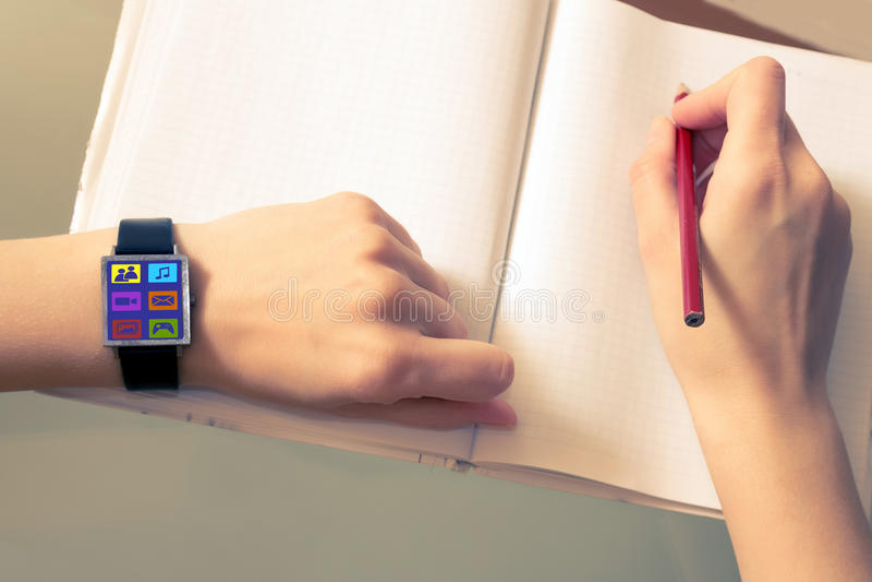 Una donna usa le reti sociali con un orologio astuto Icone della rete sociale Un orologio astuto su una mano del ` s della donna immagini stock libere da diritti
