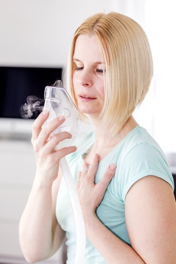 Una donna utilizza un inalatore fotografia stock
