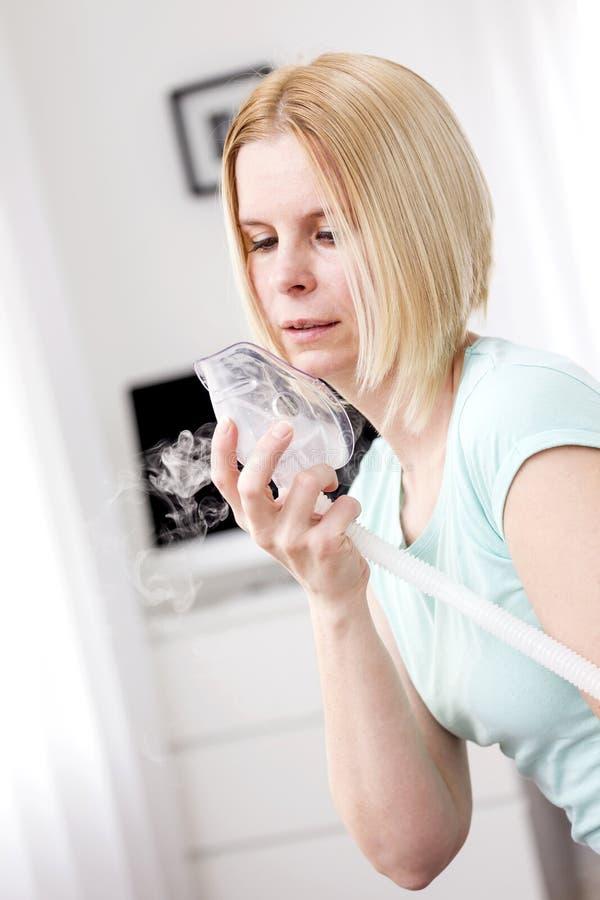 Una donna utilizza un inalatore fotografie stock libere da diritti