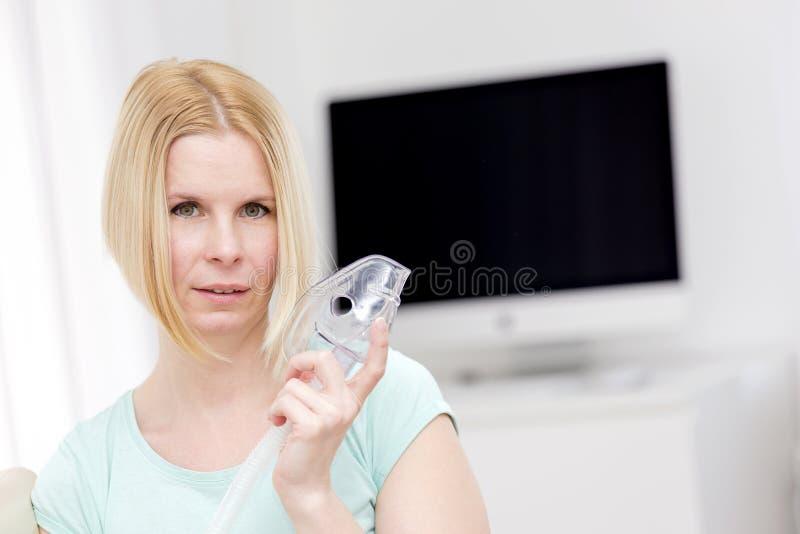 Una donna utilizza un inalatore immagine stock