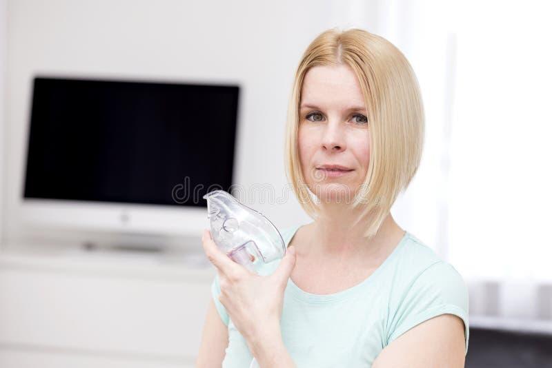 Una donna utilizza un inalatore immagini stock