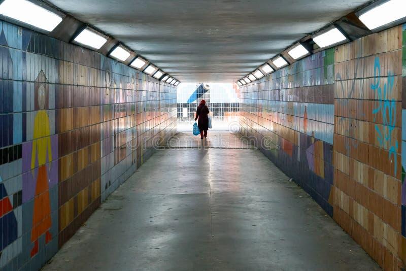 Una donna velata che cammina da solo in un sottopassaggio pedonale tenue immagini stock