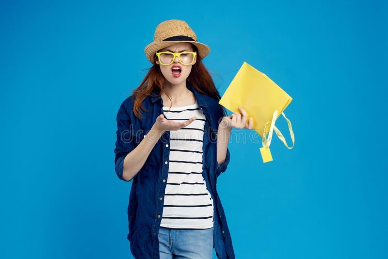 Una donna in vetri tiene un pacchetto, emozioni fotografia stock