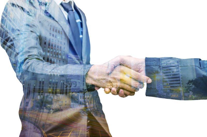 Una doppia esposizione di due uomini d'affari che stringono le mani immagini stock