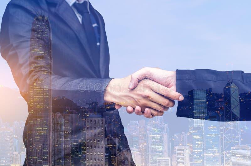 Una doppia esposizione di due uomini d'affari che stringono le mani immagine stock