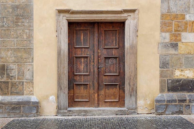 Una doppia porta di legno con la struttura di porta di rettangolo in una parete di pietra immagini stock