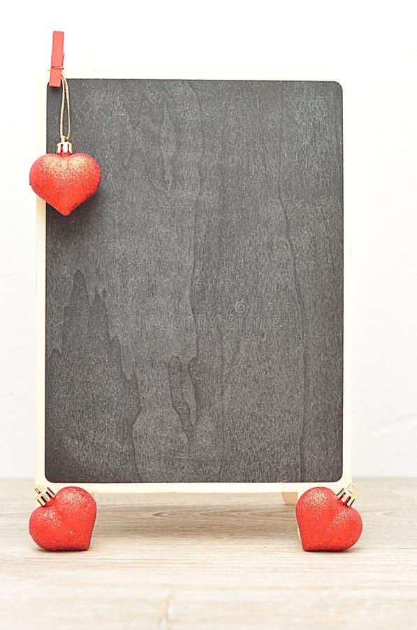 Una ejecución roja del corazón en un tablero negro con dos pequeños corazones imagen de archivo libre de regalías