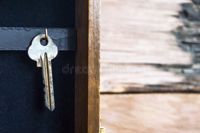 Una ejecuci?n dominante en un gancho de oro en un tenedor de la llave de la pared en fondo de madera r?stico Hipoteca, seguro, co fotos de archivo libres de regalías