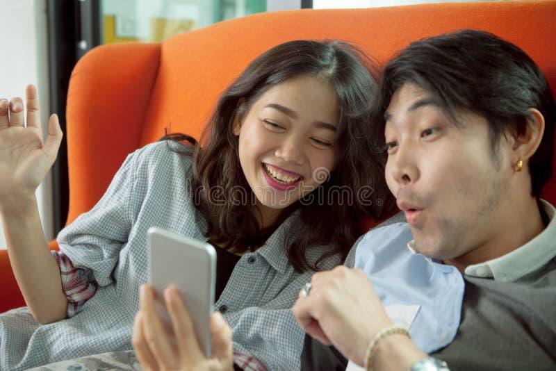 Una emoción asiática más joven de la felicidad del hombre y de la mujer al mirar en el SM fotografía de archivo