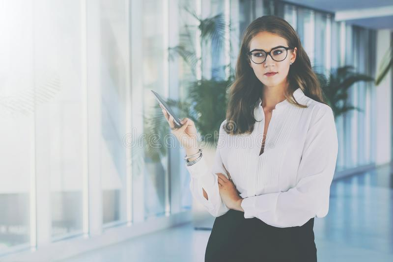Una empresaria atractiva joven en vidrios y una camisa blanca se está colocando en la oficina, usando un smartphone fotos de archivo